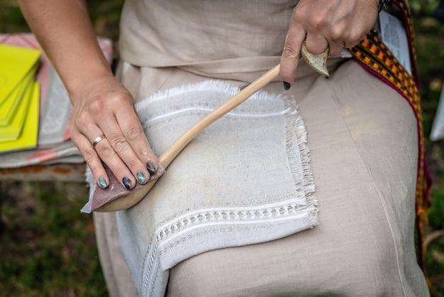 De vrouw maakt traditionele handgemaakte houten lepel.