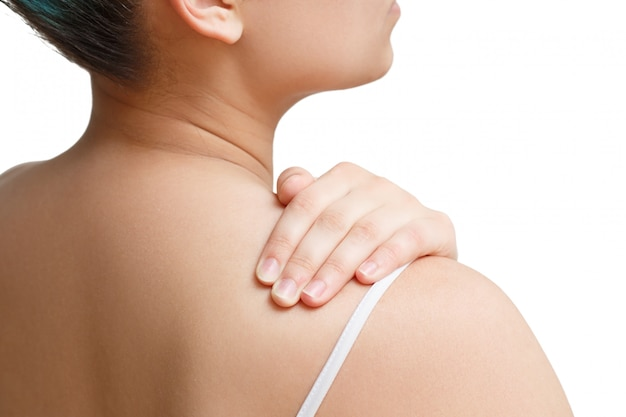 De vrouw masseert de schouder met haar hand. het uitzicht vanaf de achterkant