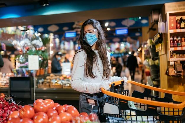 De vrouw met chirurgisch masker gaat tomaten kopen