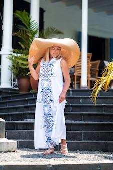 De vrouw met de grote hoed lacht. een mooi meisje in een grote hoed en een witte jurk lacht buiten een oud koloniaal gebouw op het eiland mauritius