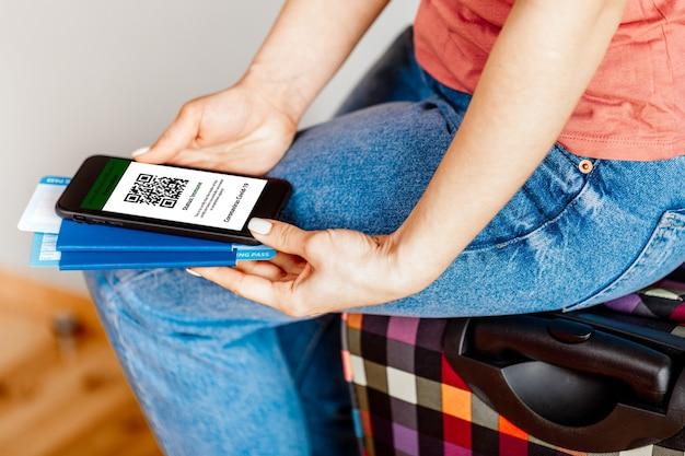 De vrouw met de mobiele telefoon een mockup voor digitaal vaccinatiecertificaat in de ene hand en paspoort, masker en ticket in een andere hand