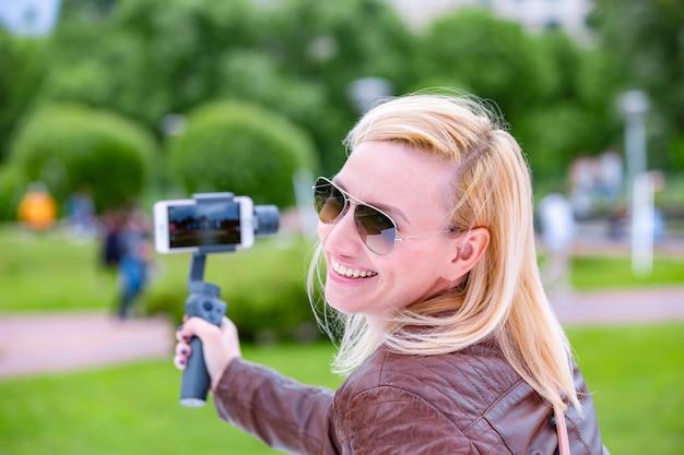 De vrouw met de telefoon op de stabilisator leidt de videoblog. ze neemt zichzelf mee naar de camera smartphone