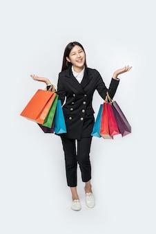 De vrouw met donkere kleding en veel tassen om te gaan winkelen