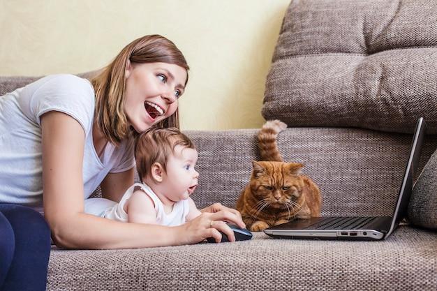 De vrouw met een baby en een kat op de laptop die op de bank ligt