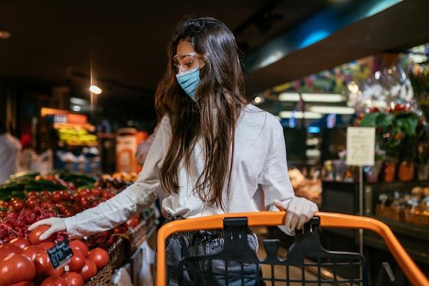 De vrouw met een chirurgisch masker gaat tomaten kopen.