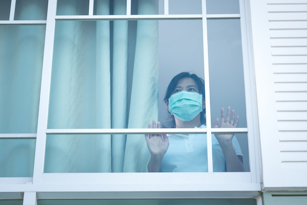 De vrouw met een medisch masker stond verdrietig naar het raam in huis te kijken voor zelfquarantaine