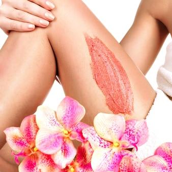 De vrouw met een mooi lichaam met bloem gebruikt een scrub op haar been op een wit