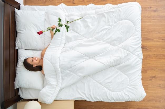 De vrouw met een roos die op het bed ligt. uitzicht van boven