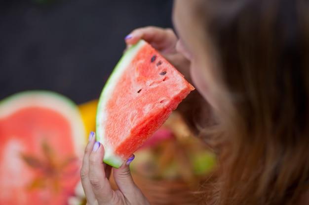 De vrouw met een stuk van rijpe watermeloen in dient een picknick in.