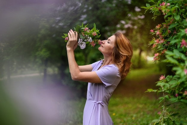 De vrouw met gesloten ogen snuift boeket van bloemen in het de zomerpark