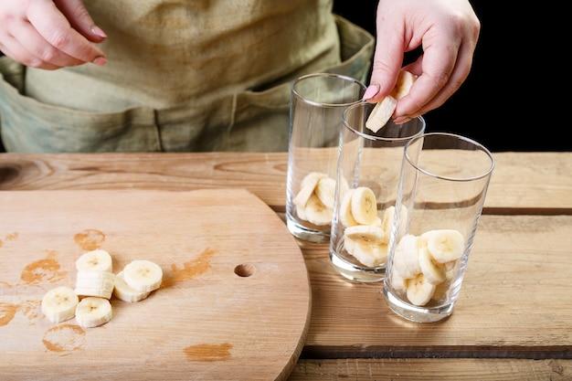De vrouw met haar hand doet de stukjes banaan in drie lege glazen glazen