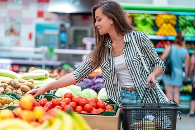 De vrouw met het winkelen mand kiest verse rode tomaten in plantaardige afdeling van supermarkt. klant het kopen van voedsel in supermarkt
