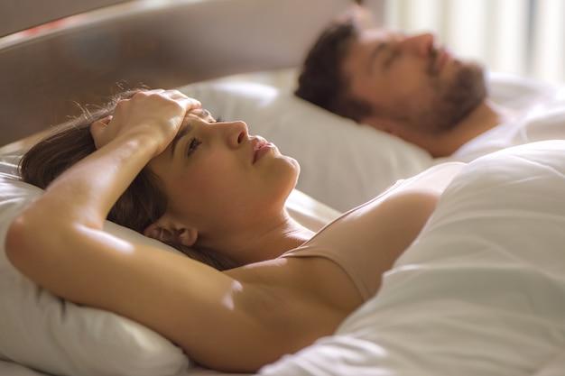 De vrouw met hoofdpijn lag naast de man in bed