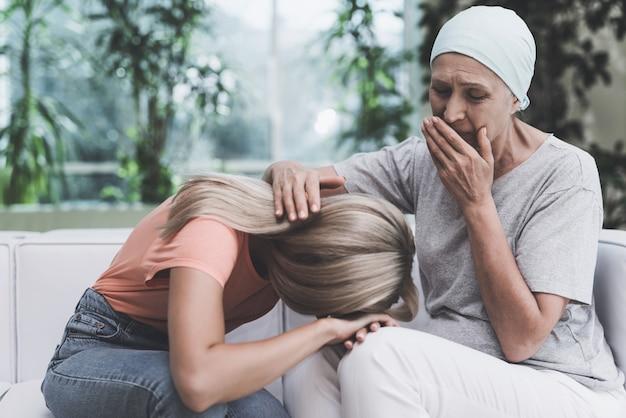 De vrouw met kanker zit op witte bank in moderne kliniek