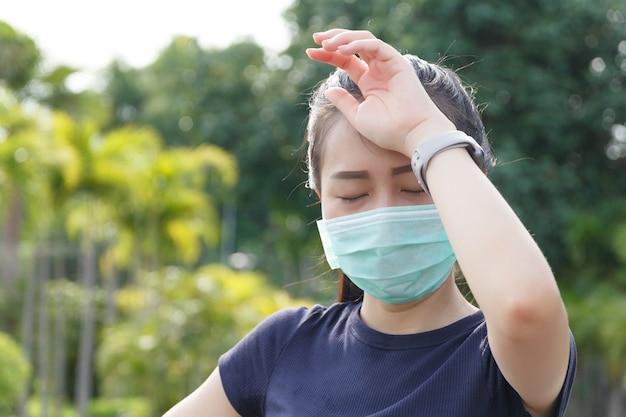 De vrouw met medisch beschermend masker, ze was moe van een trainingsrust. vrouwelijke atleet die lijdt aan hoofdpijn en duizeligheid.