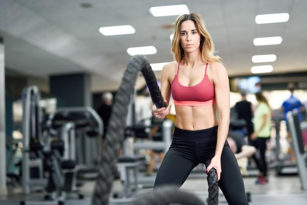 De vrouw met slagkabels oefent in de fitness gymnastiek uit.