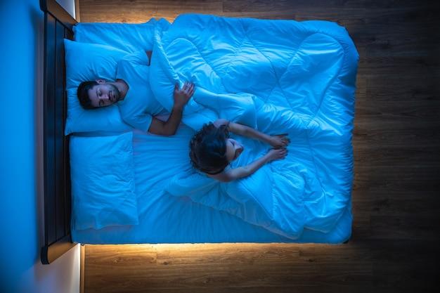 De vrouw met slapeloosheid zit in de buurt van een slapende man op een bed. uitzicht van boven