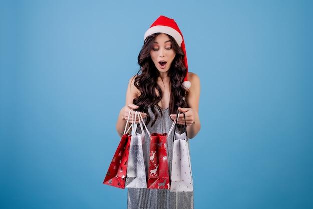 De vrouw met stelt in het winkelen zakken voor het dragen van kerstmishoed die over blauw wordt geïsoleerd