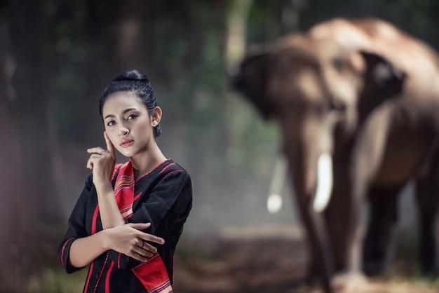 De vrouw met traditionele thaise kleding koestert haar olifant, bij olifantendorp, surin, thailand