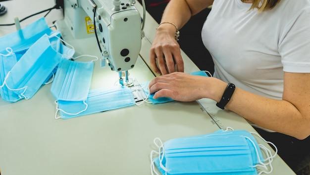 De vrouw naait gezichts medisch bij naaimachine. coronavirus pandemie.