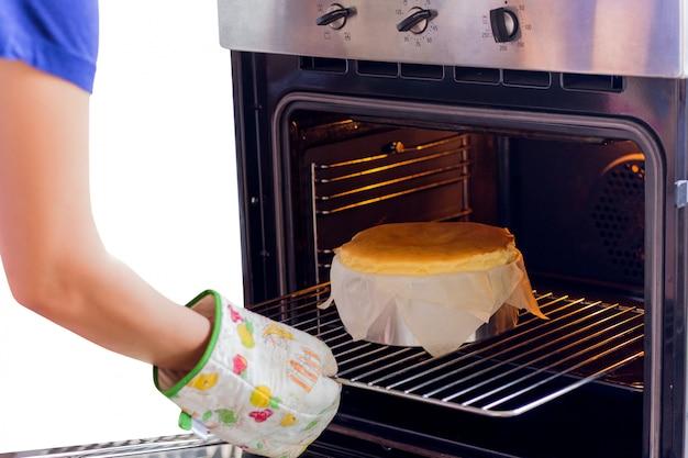 De vrouw neemt baskische gebrande kaastaart uit de geïsoleerde oven