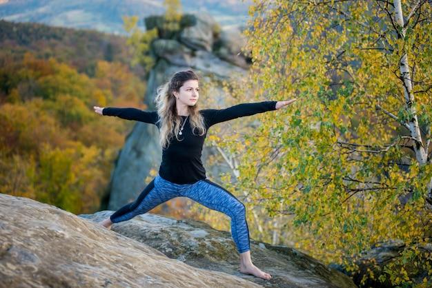 De vrouw oefent 's avonds yoga uit op de top van de hoge rotsachtige berg dichtbij boom