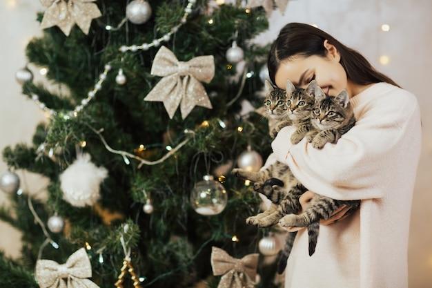 De vrouw omhelst haar kleine katjes