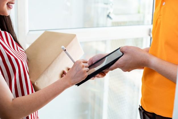 De vrouw ondertekent op een tablet om pakketten van de postbode te ontvangen.