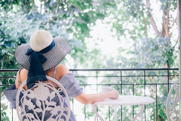 De vrouw ontspant en het drinken koffie en theezonzitting openlucht in zonneschijnlicht genietend van haar ochtendkoffie