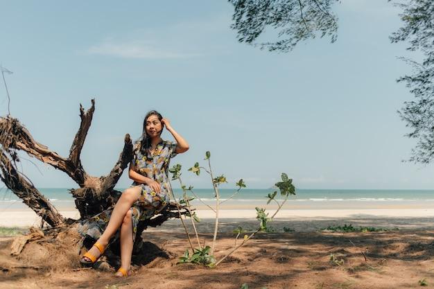 De vrouw ontspant op het strand onder de pijnboomboom in kalme atmosfeer.