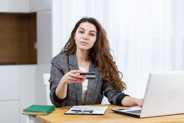 De vrouw ontspant thuis, winkelt online, gebruikt een laptop en een creditcard