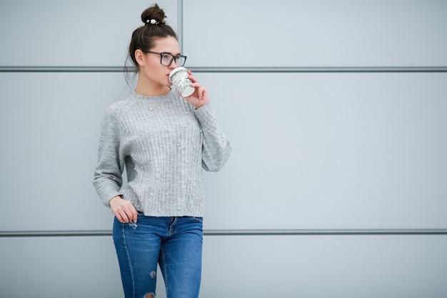 De vrouw op de achtergrond van grijze muren met lang zwart haar en een bril voor zicht