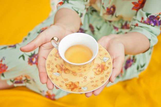 De vrouw op de picknick zit op de gele dekking en houdt kop thee.