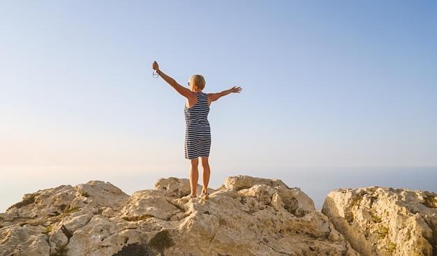 De vrouw op middelbare leeftijd in blauwe kleding begroet de dageraad van de zon