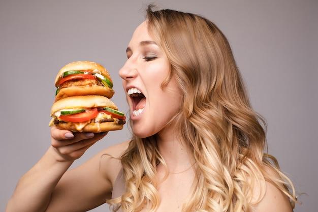 De vrouw opende haar mond om een hamburger te eten