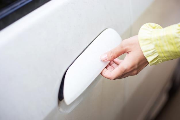 De vrouw opent en opent deur van witte auto