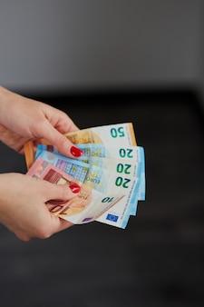 De vrouw overhandigt tellend euro geld, houdend in haar handen.