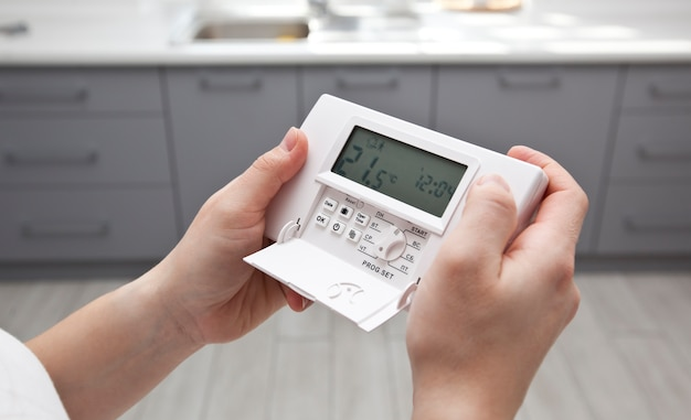 De vrouw past de thermostaat in huis aan