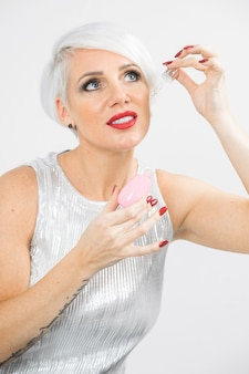 De vrouw past serum op het geïsoleerde gezicht toe