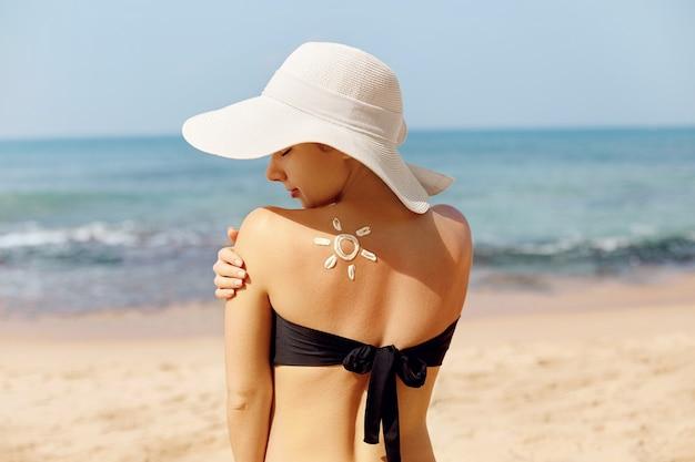 De vrouw past zonnebrandcrème op haar gebruinde schouder toe.