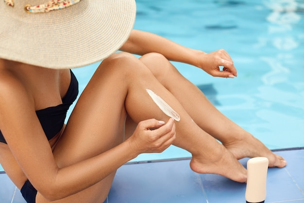 De vrouw past zonnebrandcrème toe op haar gladde, gebruinde benen