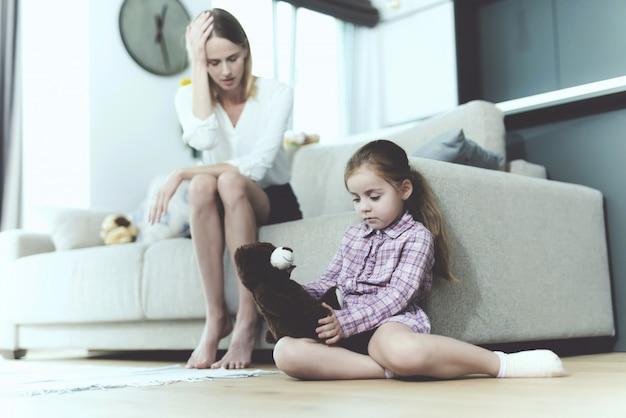 De vrouw praat met een klein beledigd meisje