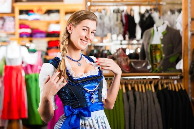 De vrouw probeert tracht of dirndl in een winkel