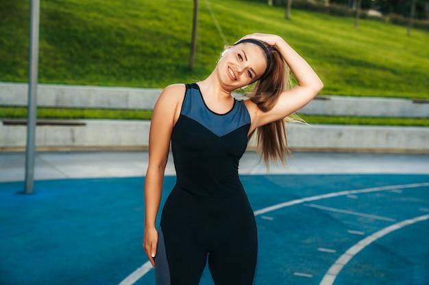 De vrouw rekt spieren in de openluchtgymnastiek uit
