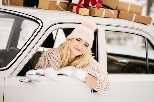 De vrouw rijdt in een retro-auto versierd met een kerstboom en presenteert in een besneeuwd bos. het concept van een winter kerst