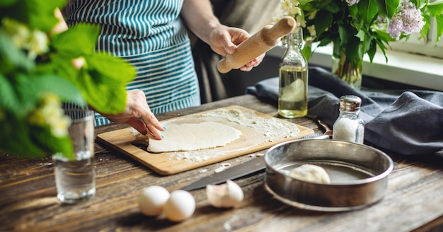 De vrouw rolt vers deeg uit om in een gezellige sfeer pasta te maken