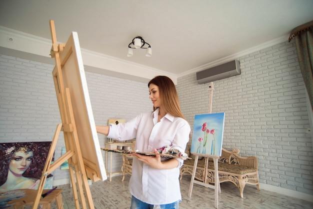 De vrouw schildert beeld op canvas met olieverven in haar studio