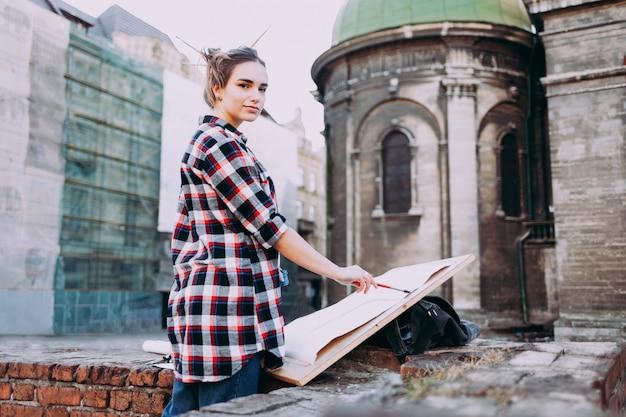 De vrouw schildert direct aan de stadsstraat tegen de achtergrond van oude architectuur.