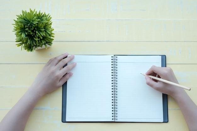 De vrouw schreef het boek met een kleiboek op een gele achtergrond. het bovenaanzicht.