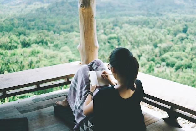 De vrouw schrijft in een klein wit memoboekje voor een notitie om niet te vergeten, van plan te zijn om te doen of een boek te schrijven met een prachtig terras met uitzicht op het huis en de natuur.